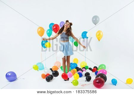 Charming young lady in trendy bright clothing looks happy holding fancy balloon bunch at party