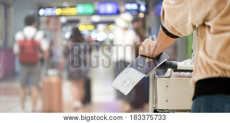 Closeup of girl holding passports and boarding pass at airport