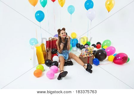 Woman fielding birthday calls, stting on floor with big helium balloons and coloured present boxes