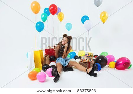 Smiling young woman in trendy clothing looks happy and glad fielding phonecalls after birthday party
