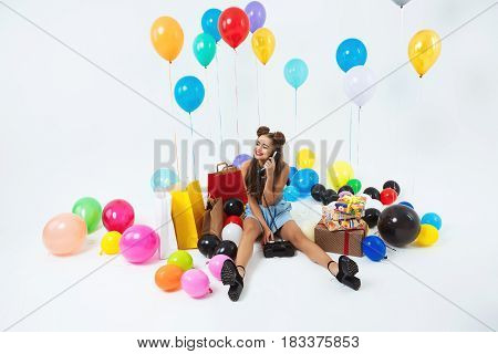 Happy teenager having big and bright birthday party receiving phonecalls from family. Sitting with presents
