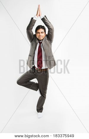 indian businessman performing yoga or asana in the office in office wear, isolated over white background