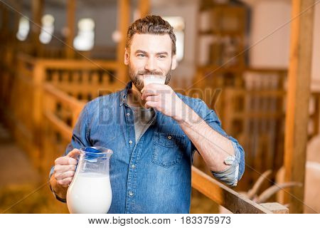 Handsome farmer tasting fresh milk standing in the goat barn. Natural milk production and farming