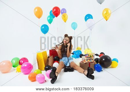 Beautiful young woman stroking long dark hair while receiving phonecalls on birthday sitting with gifts