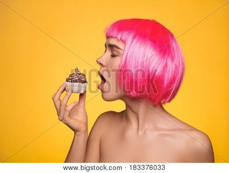 Young female model wearing pink wig and willing to eat cupcake on yellow background
