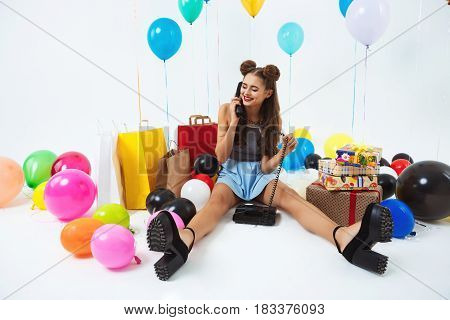 Stylish girl sitting on white floor with home phone, receiving birthday wishes, while happy partying