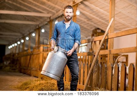 Portrait of a handsome farmer standing with retro milk container at the goat barn. Natural milk production and farming