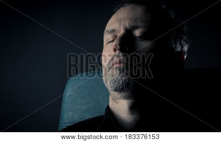 close up of a man sleeping on a leather chair
