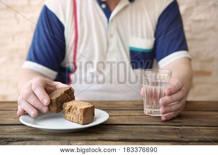 Senior man sitting at table with bread and glass of water, closeup. Poverty concept
