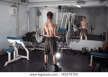 Exercise on the biceps with the barbell. A young athletic man performs. Standing with your back