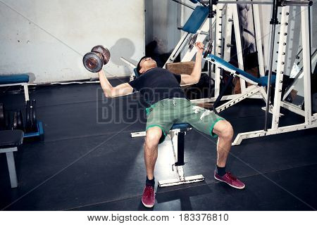 Exercise with dumbbells - wiring in the sides on an incline bench. Old gym room