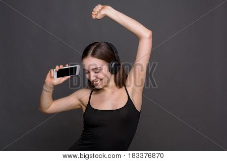 Favorite song in playlist. Woman enjoying music from mobile in earphones dancing on gray studio background