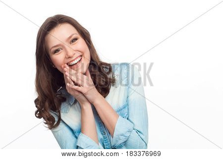 Young cheerful female in denim shirt looking at camera contently isolated on white background.