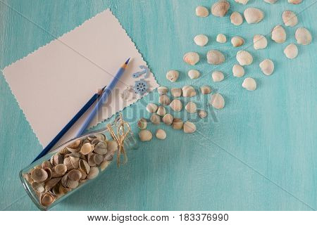 Seashells spill out of the bottle glass, sheets of paper  and pen on a blue background. Plans or memories about vacation. Place for text and inscriptions.