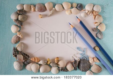 Seashells with sheets of paper  and pen on a blue background. Place for photos, place for text and inscriptions