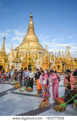 YANGON MYANMAR - DECEMBER 17 2016 : Burmese people clean the floor inside the area of Shwedagon pagoda (Shwedagon Zedi Daw) famous landmark and travel destination of Yangon Myanmar.