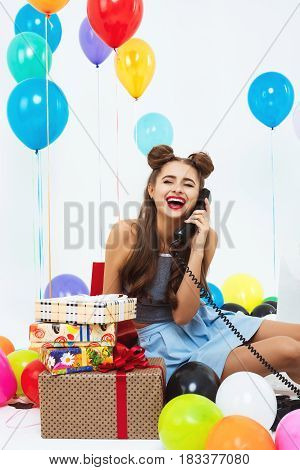 Laughing young woman sitting on floor and talking on phone, receiving birthday wishes after celebration