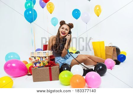 Laughing stylish girl after great birthday celebration talking on phone and receiving wishes from parents