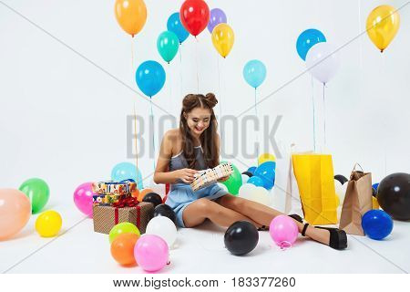 Girl in dress and with fashion hairstyle uncovering birthday present boxes sitting with helium balloons