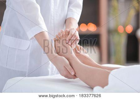 Female masseur massaging woman's foot in spa salon