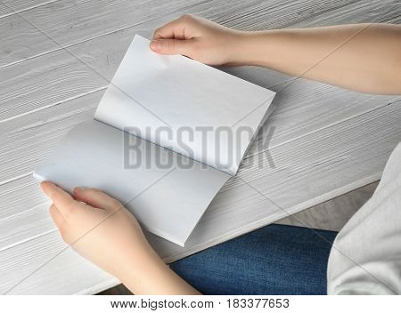 Female hands holding blank brochure on white wooden table