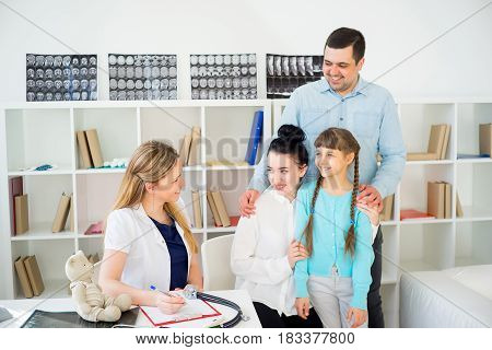 Family doctor and patients at hospital on examination
