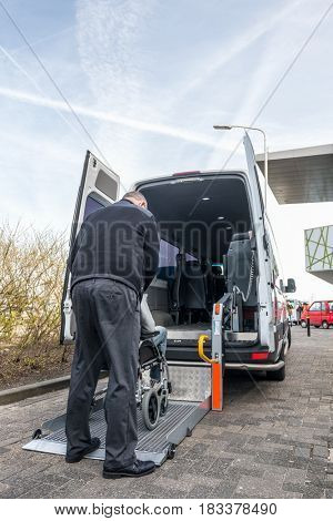 Rear view of taxi driver assisting man on wheelchair to board hydraulic lift van