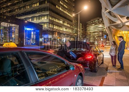 Taxi driver loading passenger luggage in car trunk on city street at night