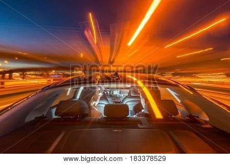Blurred motion of professional taxi driver riding couple on bridge at night