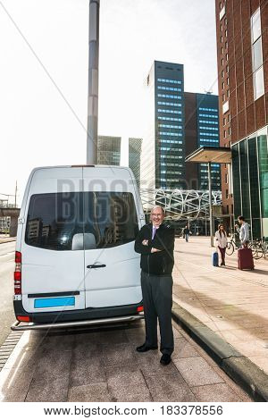 Portrait of professional taxi driver standing arms crossed by van at airport