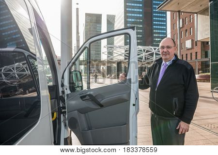 Portrait of confident male taxi driver standing by van at airport