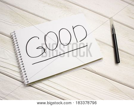A notebook with an inscription is good and black marker on white wooden table