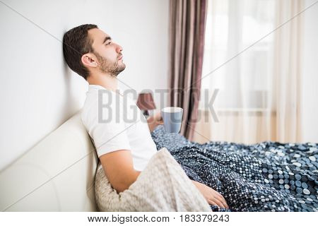 Bearded Man In Bed Drinking Morning Coffee In Sunrise Light At Home