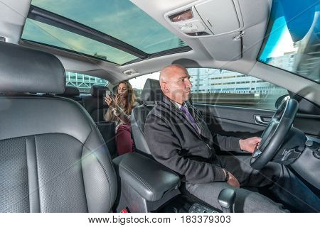 Professional driver riding taxi while female passenger applying lipstick