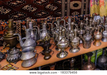 Moscow, Russia - March 19, 2017: Traditional oriental antiques brass jungs and vases at the bazaar