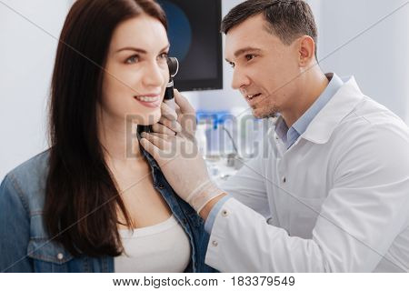 Excellent health. Handsome doctor holding otoscope in right hand keeping smile on his face while examining ear of pretty woman