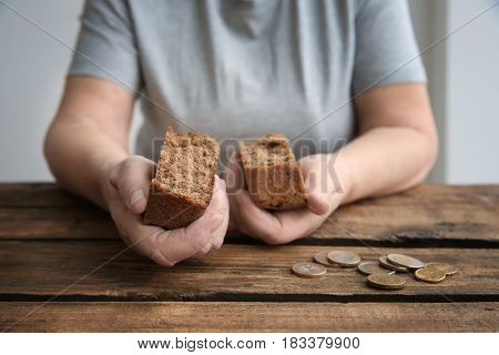 Senior woman sitting at table with bread and coins, closeup. Poverty concept