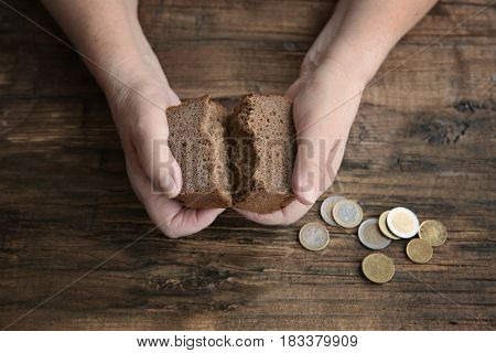 Hands of senior woman with bread and coins on wooden background. Poverty concept