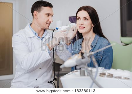 Casual style. Confident otolaryngologist wearing white smock and rubber gloves holding ENT instrument in right hand while looking at the process