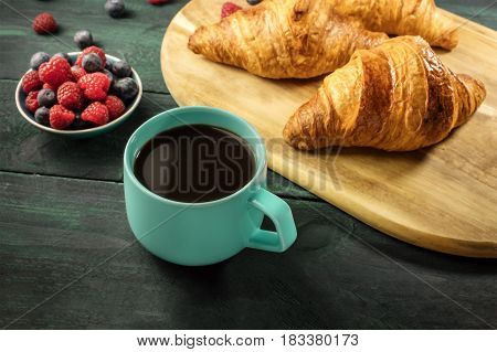 A photo of a cup of hot chocolate with crunchy French croissants and fresh raspberries and blueberries on a wooden cutting board, with a place for text. Selective focus