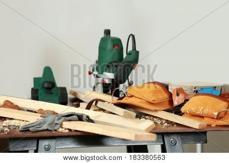 Table with wooden boards, tools and special equipment in carpenter's workshop