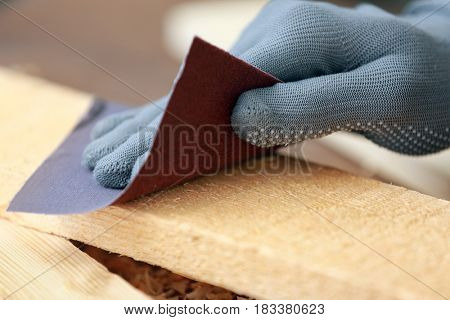 Hand of carpenter rubbing wooden board with abrasive paper, closeup