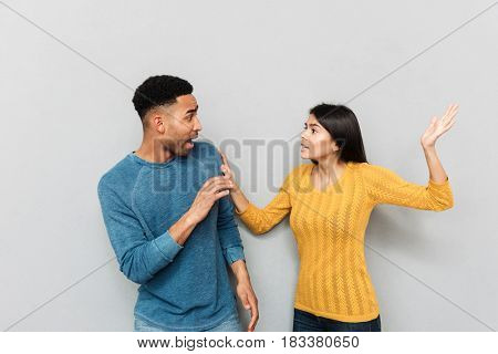 Aggressive wife beating her frightened african husband isolated