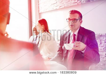 Mature businessman having coffee while talking with male colleague in office cafeteria