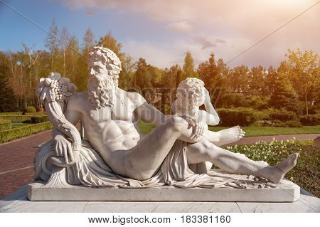 Marble statue of greek god with cornucopia in his hands