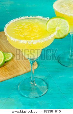 Lemon Margarita cocktails with wedges of lime on a turquoise background with copy space