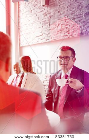 Mature businessman having coffee while sitting with male colleague in office cafeteria