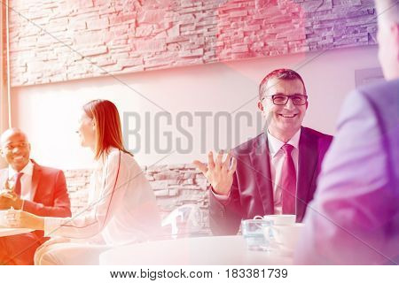 Smiling mature man talking with male colleague in office cafeteria