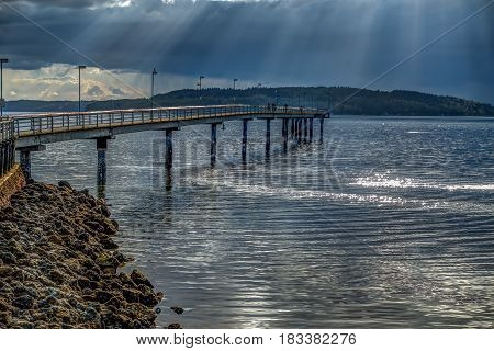 Rays of light shine through clouds in Des Moines Washington. HDR image.