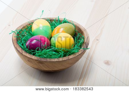 Four Hand Painted Easter Eggs On A Wood Bowl On A Pine Wood Table